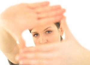 Frau hält ihre Hände so vors Gesicht, dass nur ihre Augen sichtbar sind wie im Visualtraining