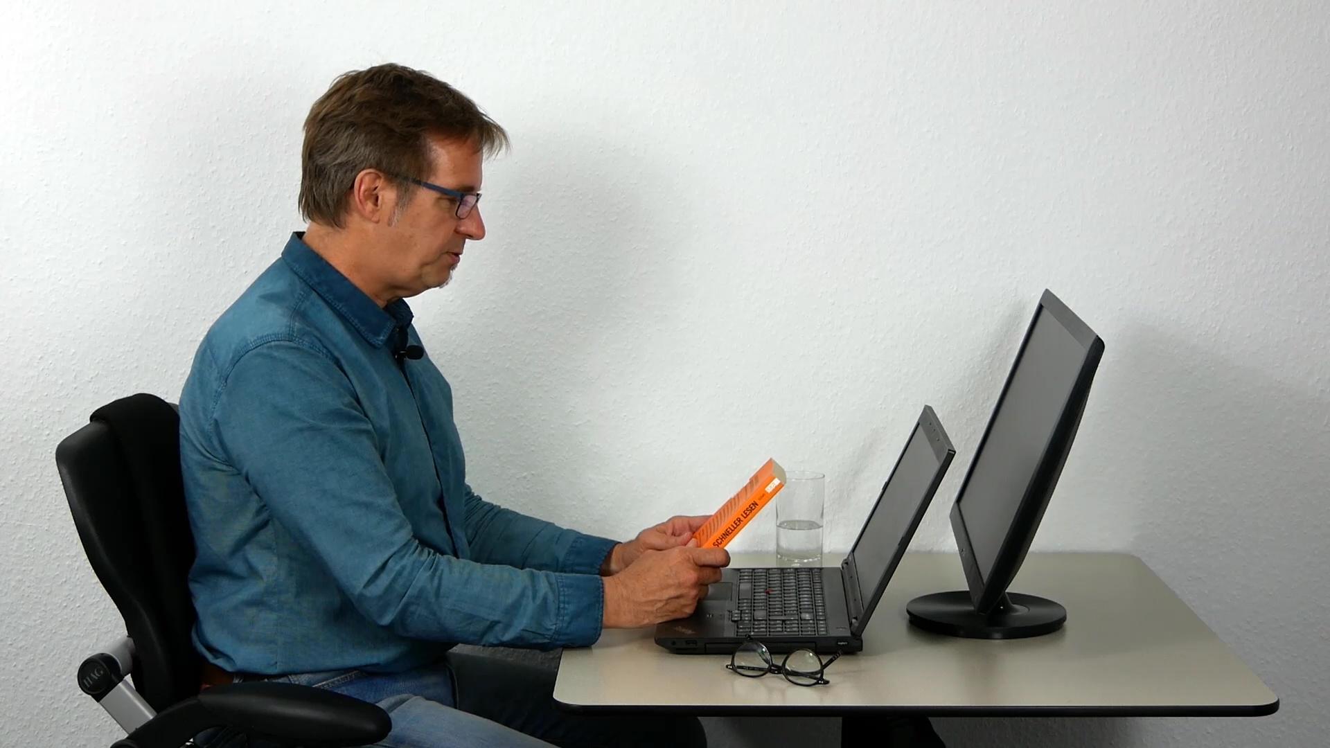 Ergonomie: Thomas sitzt vor einem Laptop, er zeigt die korrekte Bildschirmneigung. Dahinter steht ein größerer Bildschirm mit etwas geringerer Neigung.