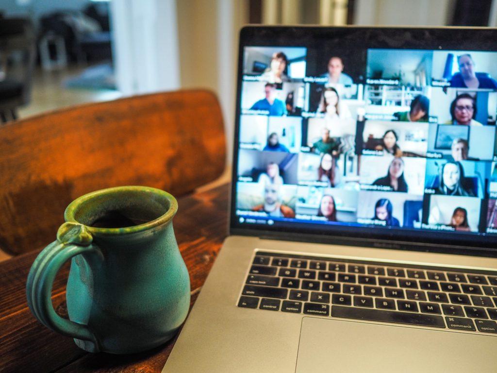 Homeoffice-Szenario, bei dem eine Videokonferenz auf einem Laptop-Bildschirm zu sehen ist
