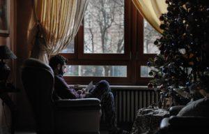 Genusslesen in der Weihnachtszeit - Mann sitzt in Lesesessel am Fenster bei Weihnachtsbaum