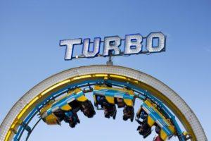 Kopfstand-Technik als Kreativitäts-Turbo in verteilten Teams; Menschen in einer Achterbahn, deren Wagen kopfstehen
