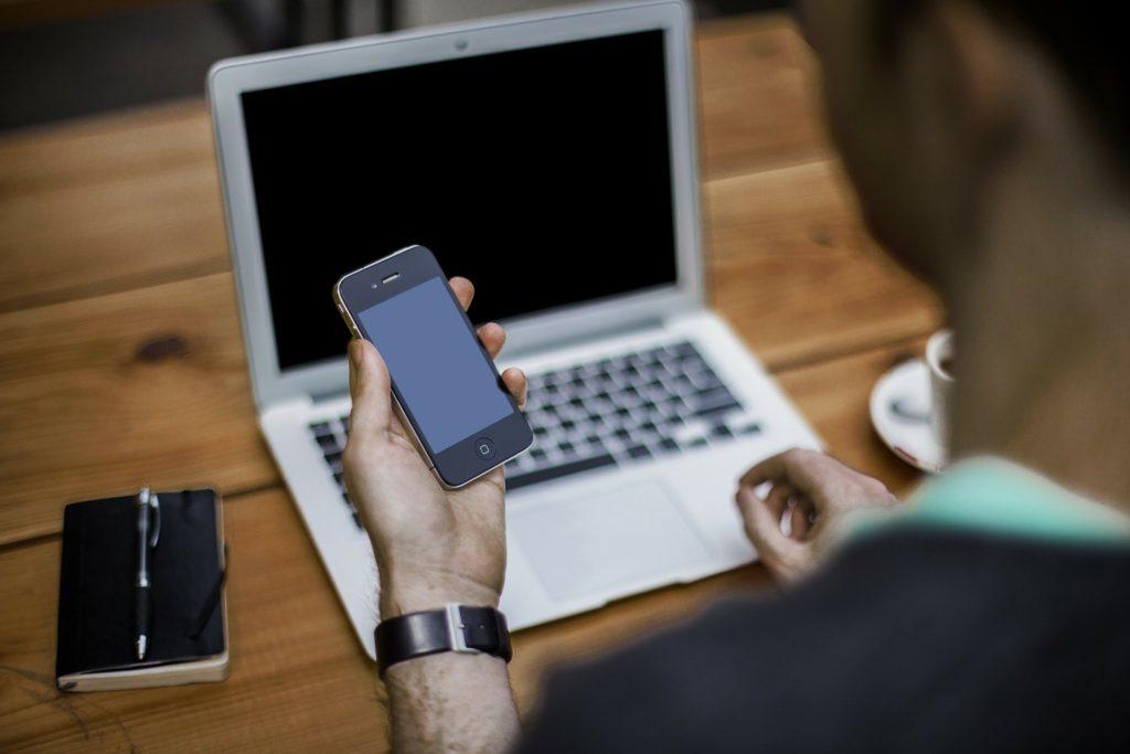 Mobiles Arbeiten: Mann im Homeoffice an Laptop und Handy. Neben ihm liegt ein Notizbuch mit Stift und eine Kaffeetasse steht auf dem Tisch.