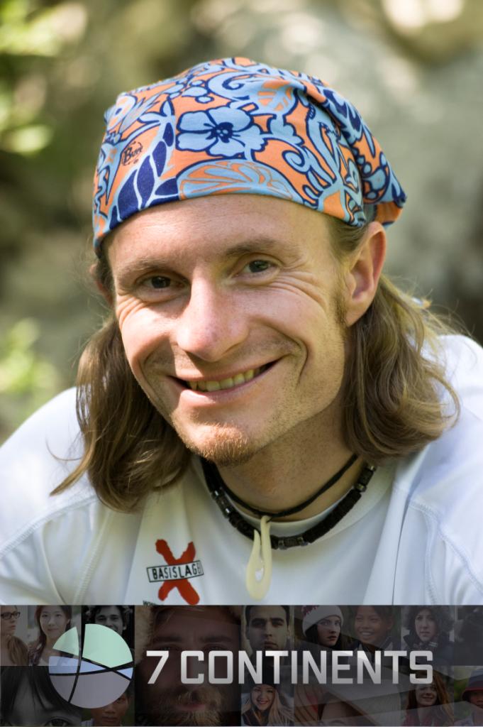 Portrait von Norman Bücher - er trägt ein schlauchförmiges Kopftuch auf seinen halblangen Haaren und ein weißes T-Shirt. Er lächelt in die Kamera.