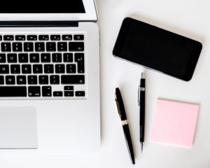 Hilfreich bei Unterbrechungen: Computer, Telefon und Notizzettel mit Stiften.