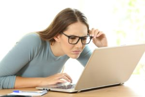 Was tun bei Nacken- und Schulterverspannungen; Frau mit Brille schaut sehr angestrengt auf den Bildschirm eines Laptops. Ihre Haltung ist ungesund.