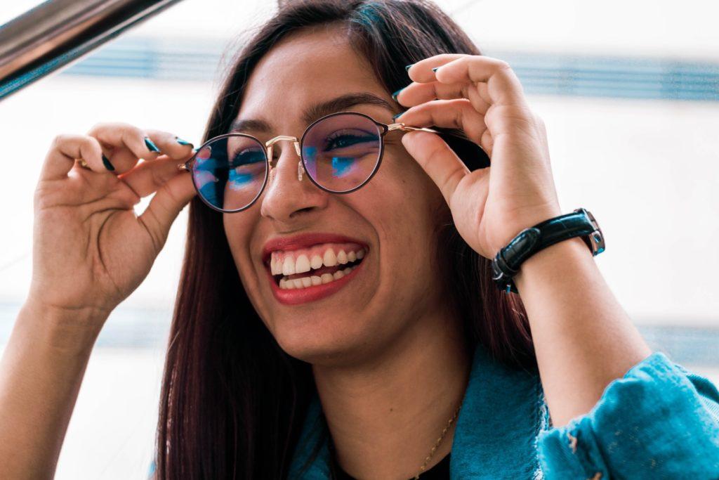 Tipps für entspanntes Sehen: Frau mit Arbeitsplatzbrille, in der sich ein blauer Bildschirm spiegelt