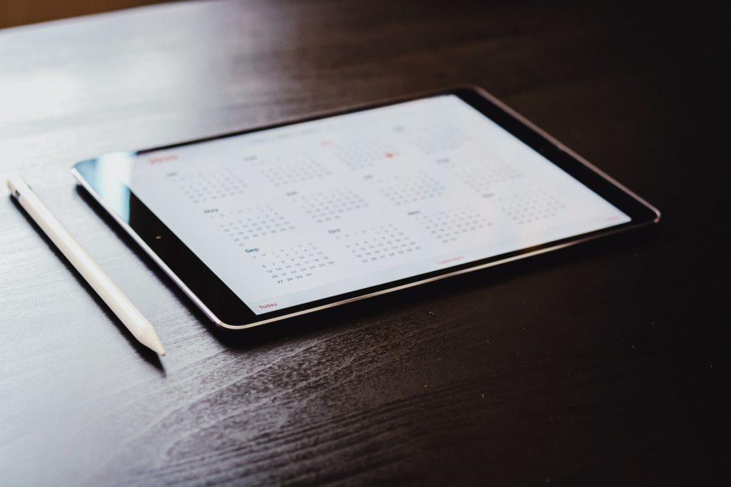 Weiterbildung sicher planen; ein Tablet liegt auf einem dunklen Holztisch. Es ist in der Kalenderansicht geöffnet.