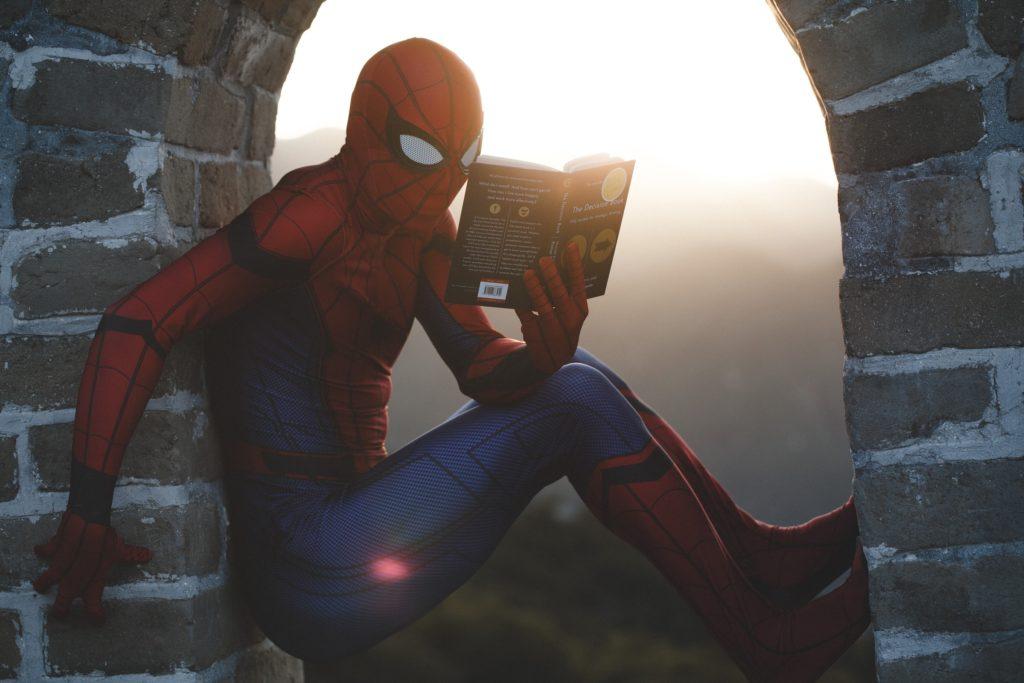 besser konzentrieren beim Lesen; Ein als Superheld verkleideter Mensch sitzt in der Fensteröffnung einer Art Burg und liest